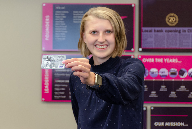 Lady smiling holding a Citizens First Bank Visa gift card